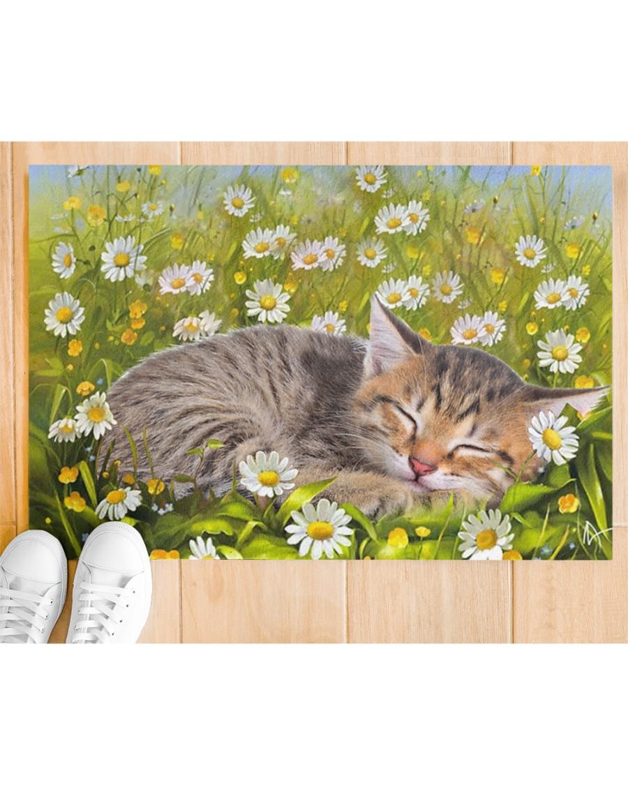 Cat sleeping on flower garden doormat Picture 1